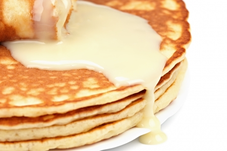 condensed: Pancakes close up watered with condensed milk