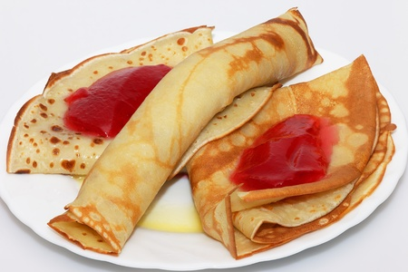 Pancakes, folded on a plate with red currant jelly  photo