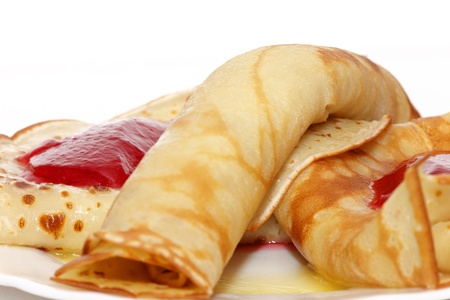 Pancakes, folded on a plate with red currant jelly, close up  photo