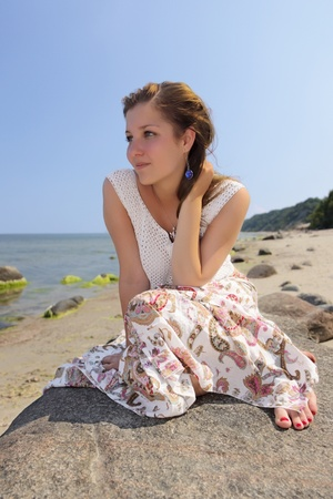 Barefoot girl in a long skirt sitting on a boulder on the beach  photo
