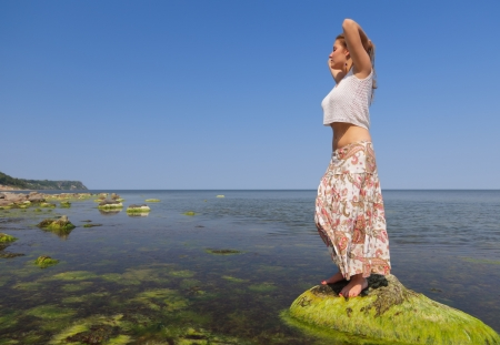 long skirt: Barefooted girl in a long skirt standing on a sea boulder covered with seaweed