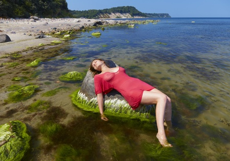 woman beach dress: Girl in a red dress lies on a stone in water