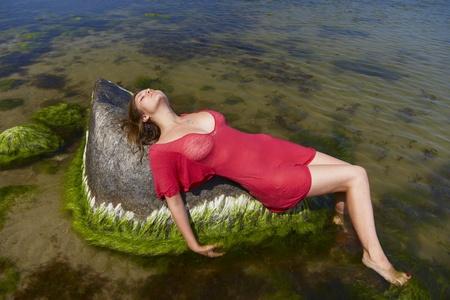 Fille dans une robe rouge se trouve sur une pierre dans l'eau Banque d'images