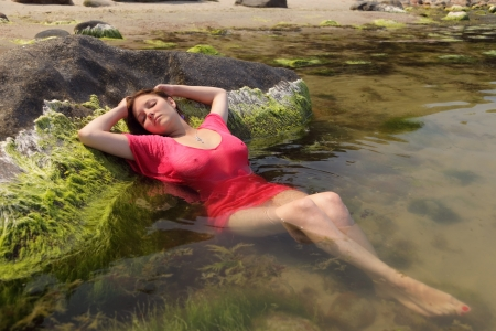 underwater woman: Girl in a red dress lies on a stone in water