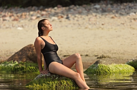 underwater woman: Girl in a black swimsuit sits  on a stone in water at a beach Stock Photo