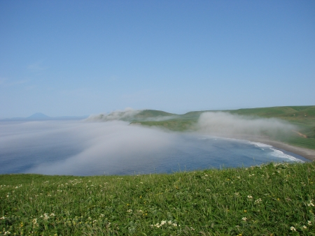 approaches: The island Urup, Russia, on July, 5th, 2007, steep coast, from passage Fruze approaches a fog