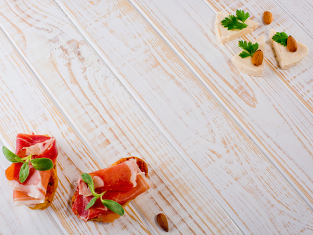 Two bruschetta sandwiches with jamon, green sprouts, almond and cheese on white wooden background.  Frame.