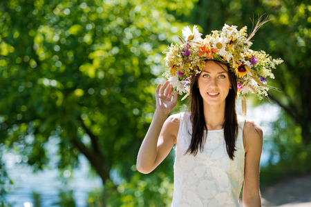 Portrait of a beautiful brunette girl in a wreath of flowers.