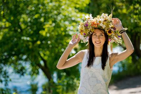 Portrait of a beautiful brunette girl in a wreath of flowers.