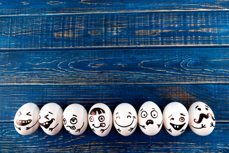 Funny easter eggs with different funny faces on blue wooden background. Top view. Stock Photo