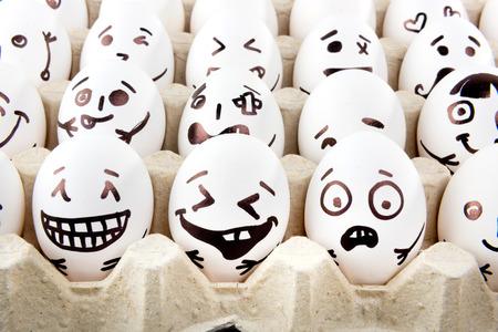 Ovos com rostos desenhados dos desenhos animados na bandeja.