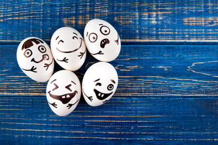 Funny Easter Eggs With Different Faces On Blue Wooden