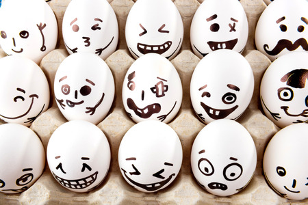 Eggs with drawn cartoon faces in tray. Stock Photo