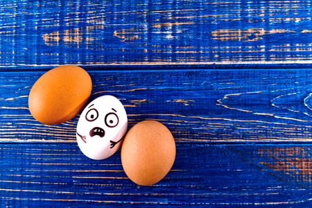 Funny easter eggs with scared face on blue wooden background. Stock Photo