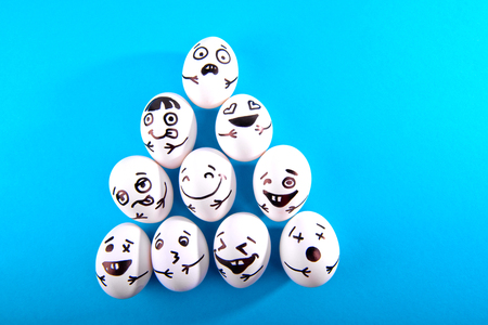Easter eggs with different funny faces on blue background with copy space. Top view. Stock Photo
