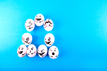 Funny easter eggs with different funny faces on blue background with copy space. Top view.
