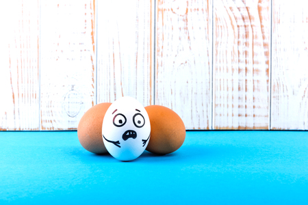 Easter eggs with scared face on blue and white wooden background.