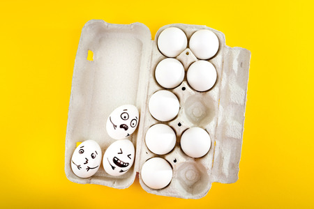 Easter eggs with drawn cartoon faces in tray on yellow background.