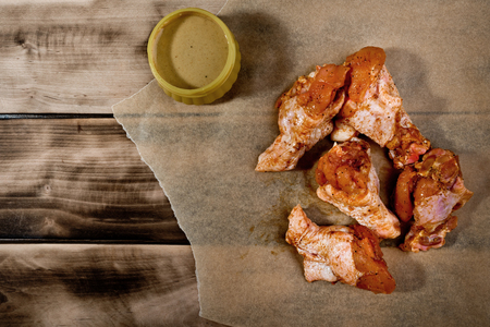 Raw marinated chicken wings on parchment -  ready for cooking. Stock Photo