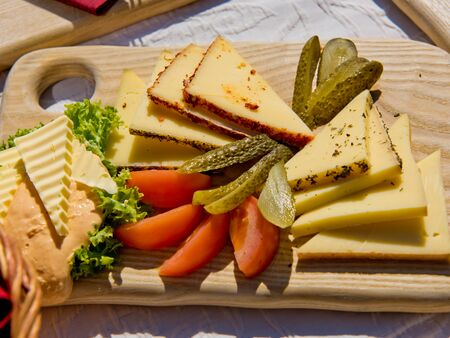 Cheese and vegetable slices on a wooden board. Stok Fotoğraf