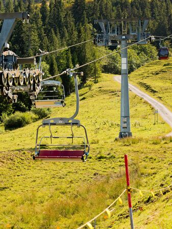 Mountain landscape with forest and ski lift on a sunny day. Stock Photo