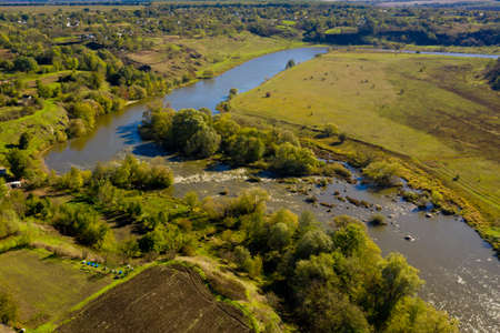 Beautiful scenery on the river and village. Aerial view. Фото со стока