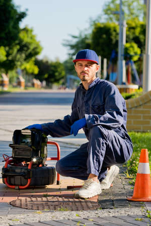 Plumber diagnoses a drain well on the street using special equipment.