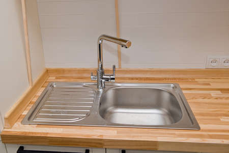 Modern faucet with steel sink.