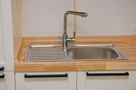 Modern faucet with steel sink. Kitchen interior. Фото со стока