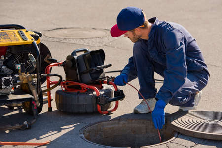 Plumber prepares to fix the problem in the sewer with portable camera for pipe inspection and other plumbing work.