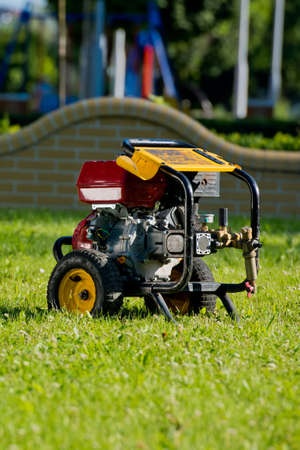 Motor pump on the lawn. Plumbing Tools. Everything for cleaning the sewer. Фото со стока