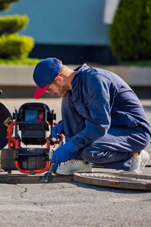 The plumber with portable camera for pipe inspection and other plumbing work.