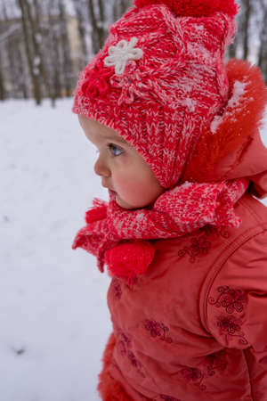 Toddler girl who walking by snow in the park. Frost winter season.