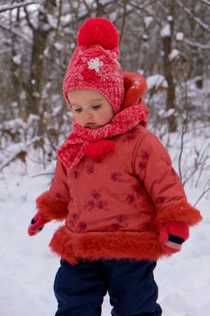 Baby girl walking on snow. Winter time.