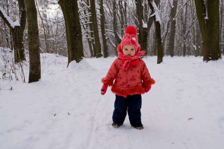 Baby girl in red jacket walking by snow in the forest.