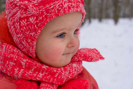 Baby girl impressed with the snow. Close-up.