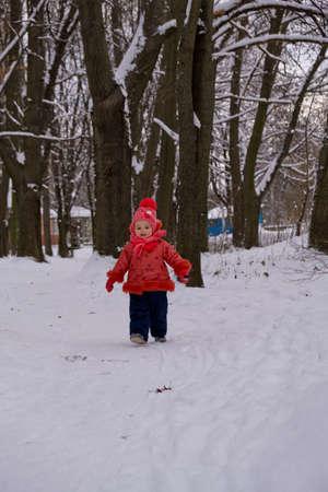 Little kid girl running on snow.