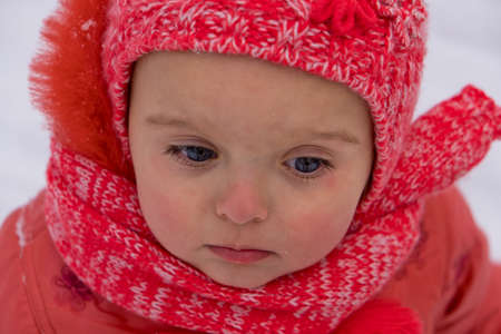 Portrait of toddler girl who walking by snow in the park. Close-up.