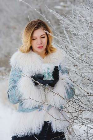 Winter portrait of smiling young woman in snowy forest.