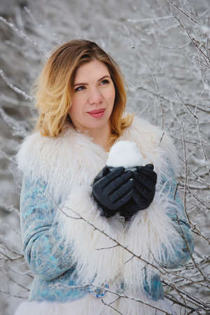 Portrait of beautiful young woman with cup of snow in hands.