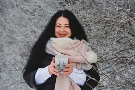 Winter portrait of smiling young brunette woman in snowy forest. Фото со стока