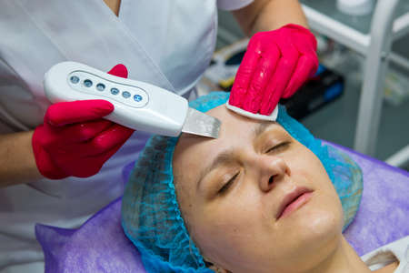 Young woman in beauty salon doing ultrasound peeling and facial cleansing procedure. Close-up. Фото со стока