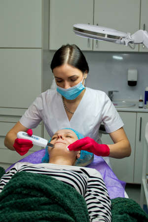 Young woman in beauty salon doing ultrasound peeling and facial cleansing procedure. Фото со стока