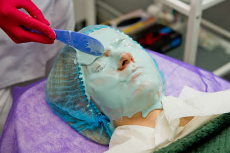Beautician in red gloves applies alginate mask on face of woman. Close-up. Фото со стока
