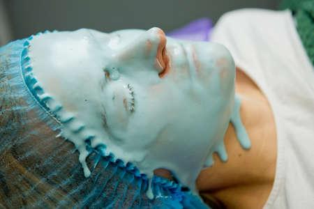 Alginate mask on face of woman. Close-up. Фото со стока