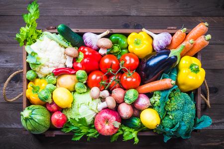 Verduras y frutas en caja de madera sobre fondo rústico. Foto de archivo