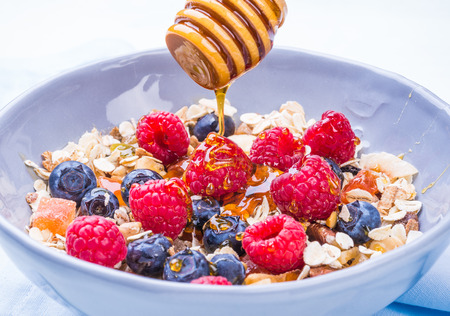 frutas deshidratadas: Healthy breakfast bowl with cereals, berries, dried fruits, honey, healthy diet concept.