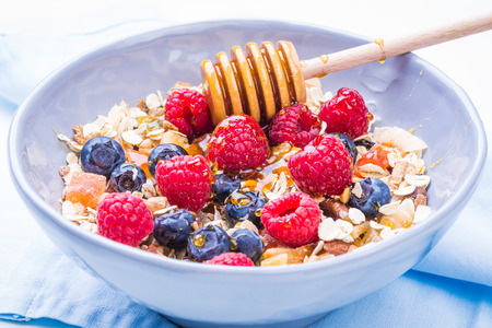 frutas deshidratadas: Healthy breakfast bowl with cereals and berries, dried fruits, honey, health and diet concept.