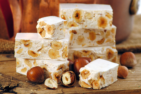 Nougat or nougat with nuts on wood background.
