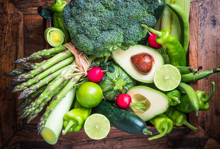 Fresh green organic vegetables on rustic dark wood background.Vegan food concept. Stock Photo